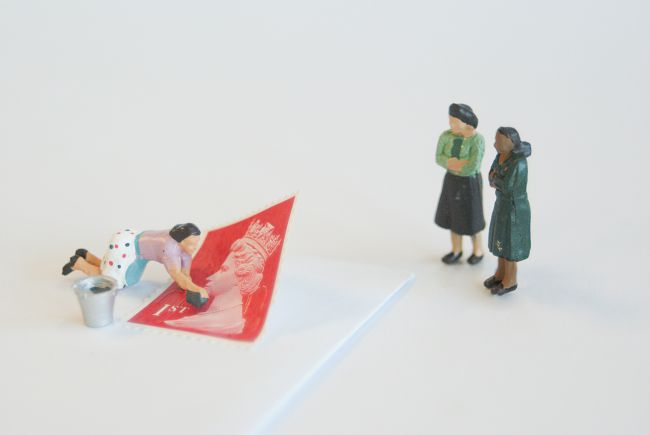 Small model figures adding a stamp to a letter