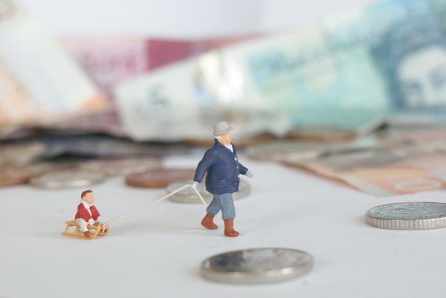 Small model figures walking past bank notes