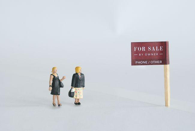 Small model figures beside a for sale sign