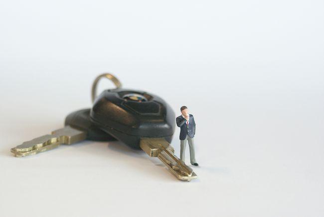 Small model figure standing beside car keys
