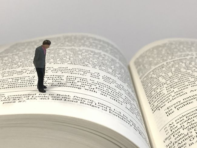 Small model figure standing on a book