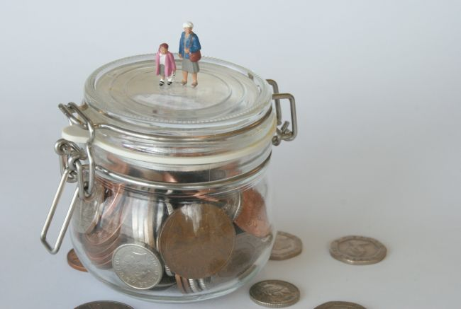 Small model figures standing on glass jar filled with coins