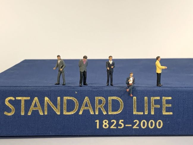 Small model figures standing on a book titled Standard Life