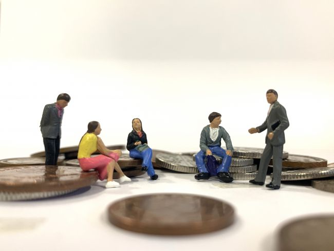 Small model figures sitting around small piles of coins