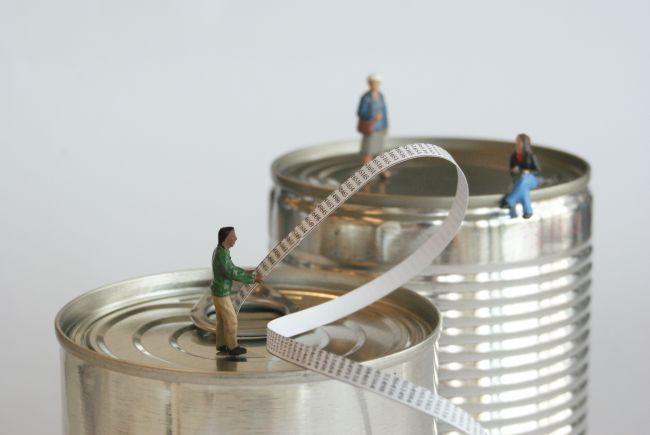 Small model figures sitting on metal food tins