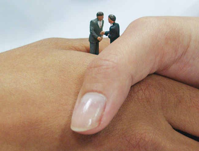 Small model figures shaking hands