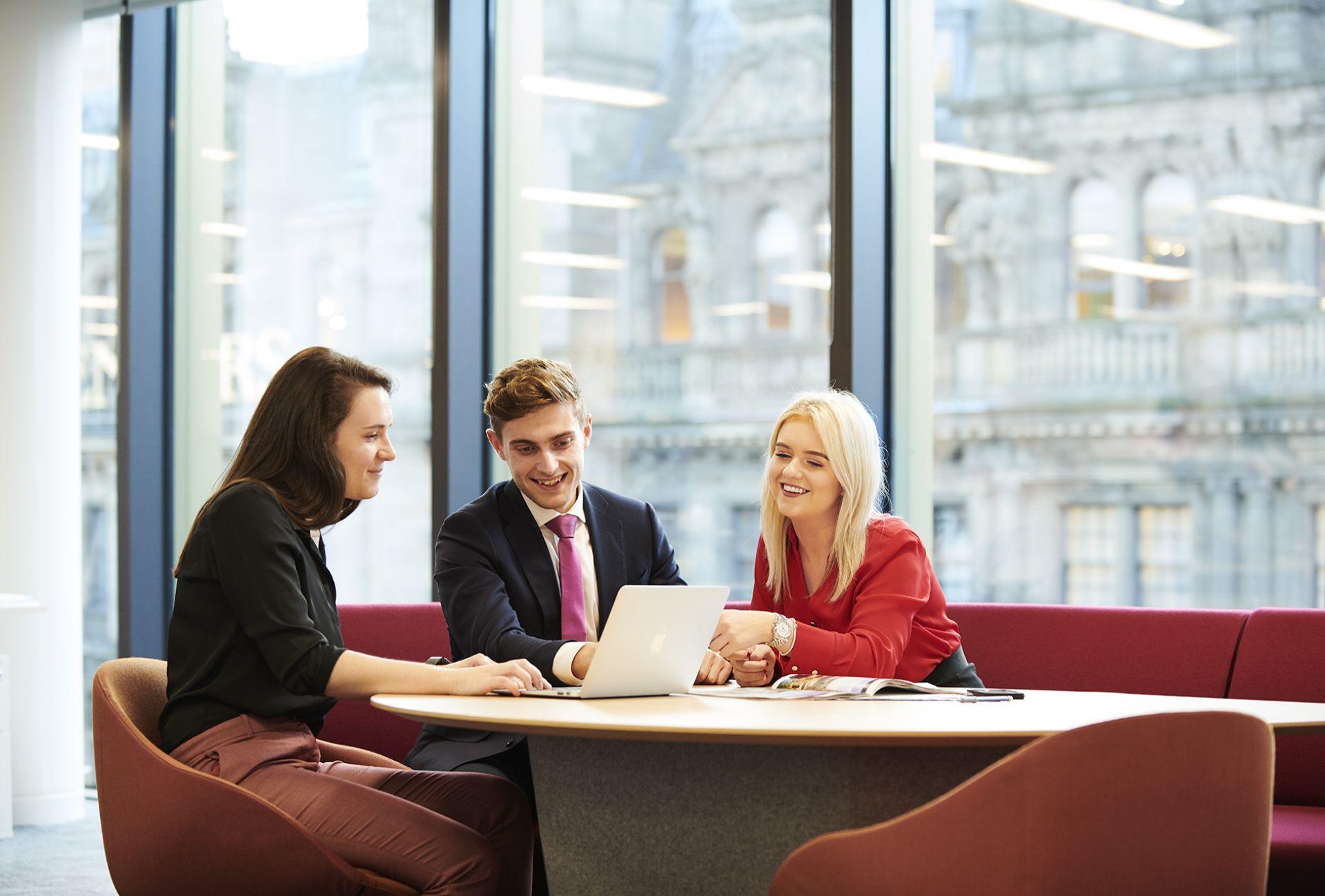 three people sitting round an office desk