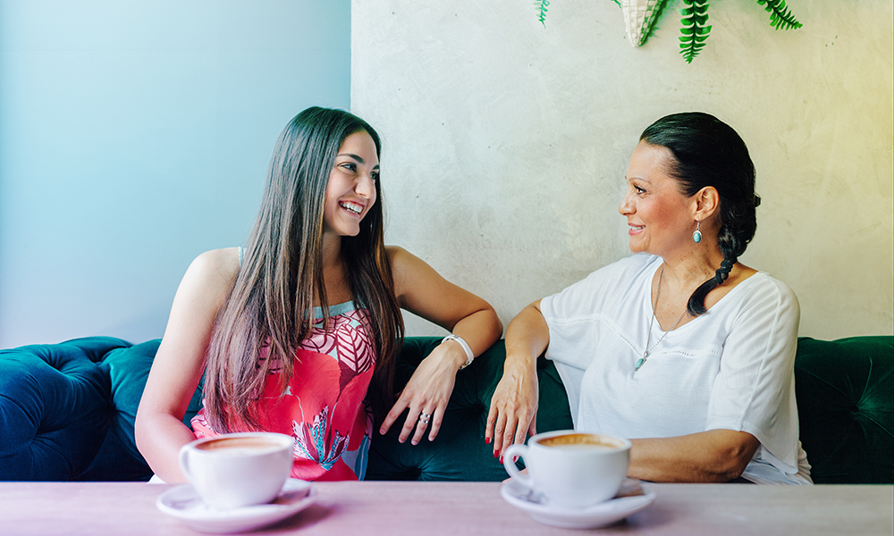 Mother and daughter having a conversation over coffee