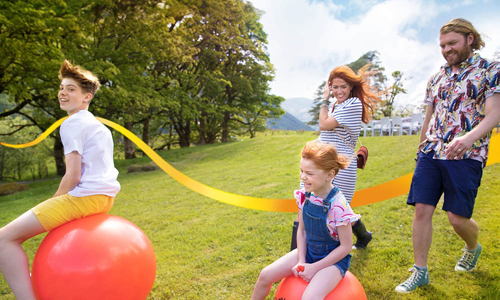 Happy family outdoors with children on spacehoppers