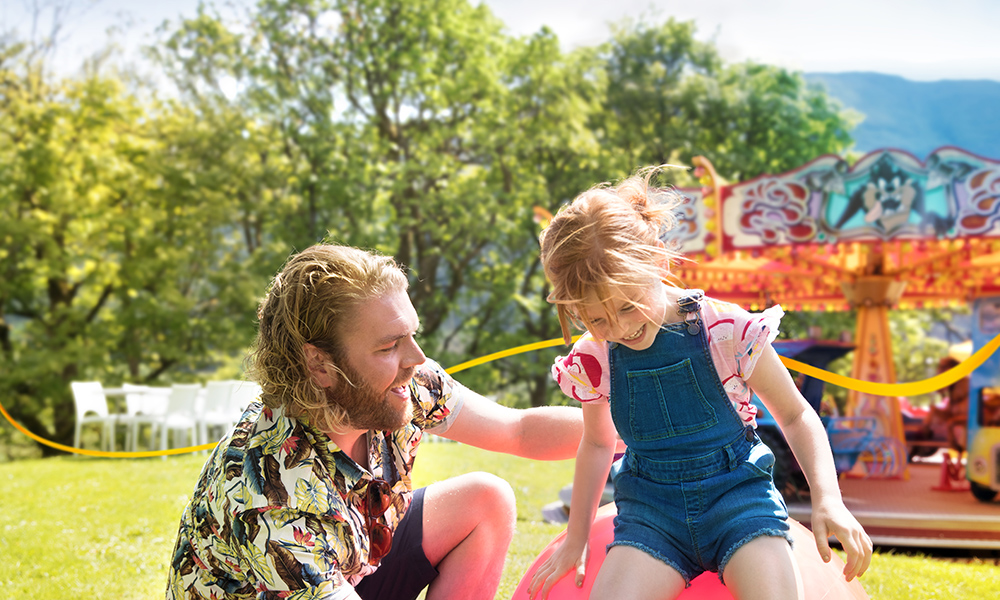 Father and daughter on bouncing ball with funfair in background