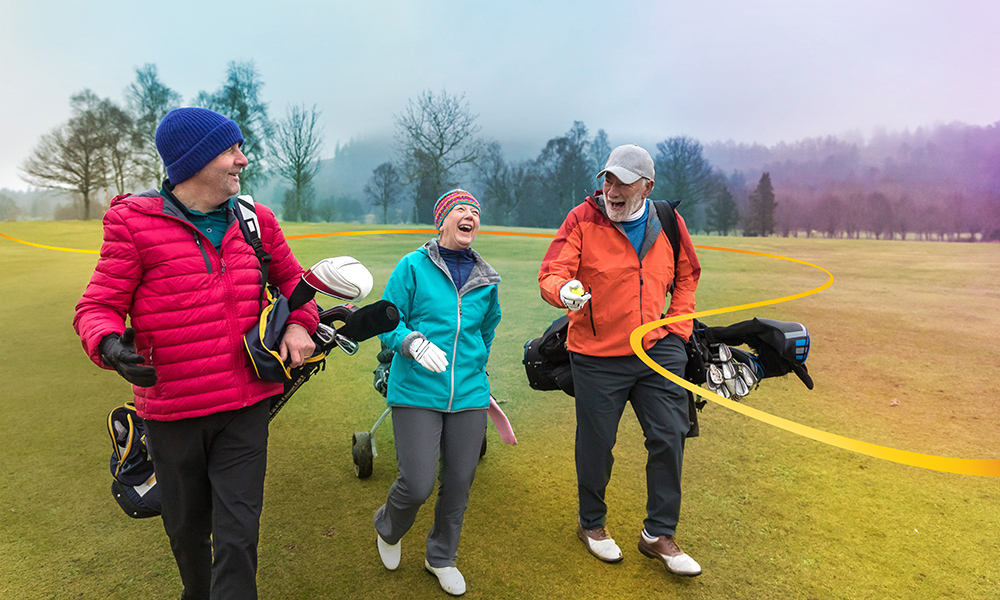 Three friends in conversation smiling and laughing as they walk on the golf course