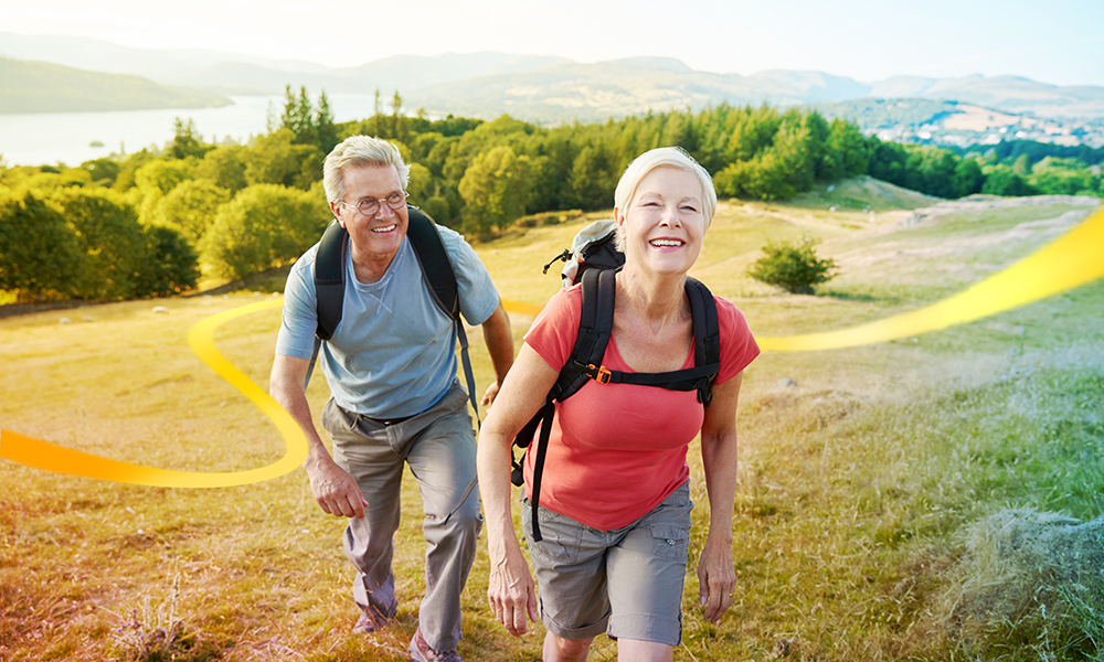 Mature couple with backpacks smiling as they enjoy their hike