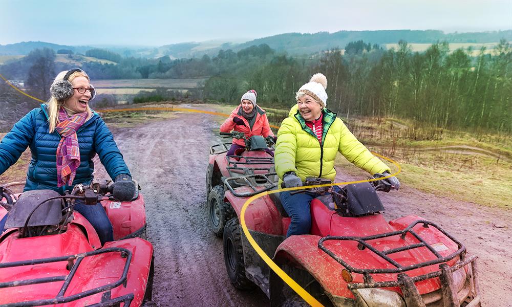 Three women riding quadbikes laughing and having fun