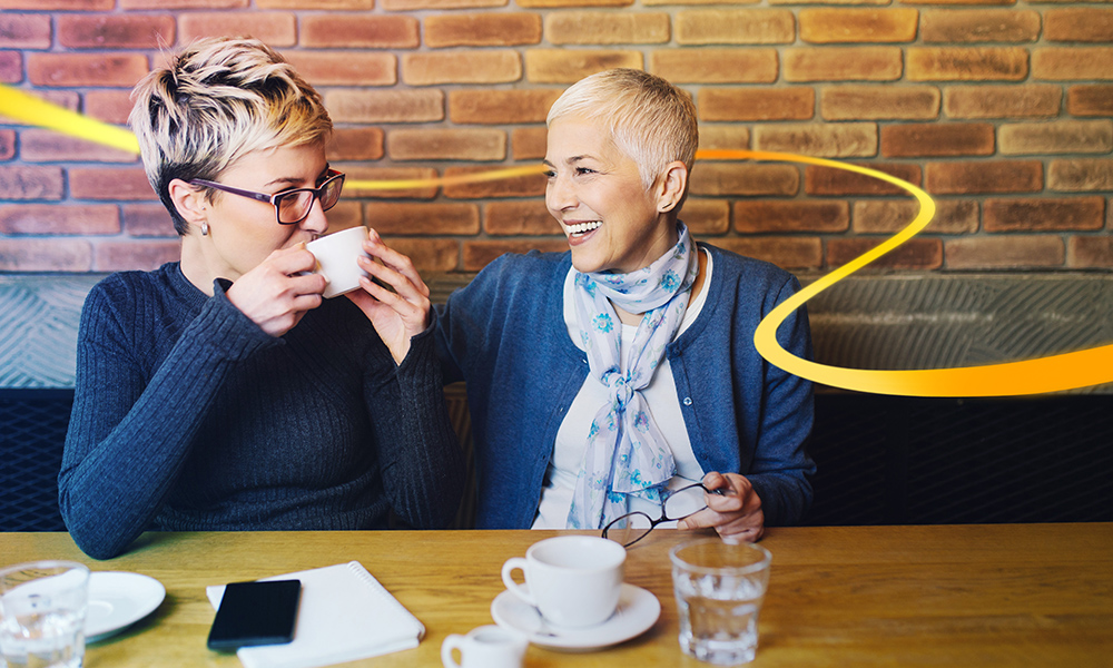 Two women in a coffee shop in conversation smiling