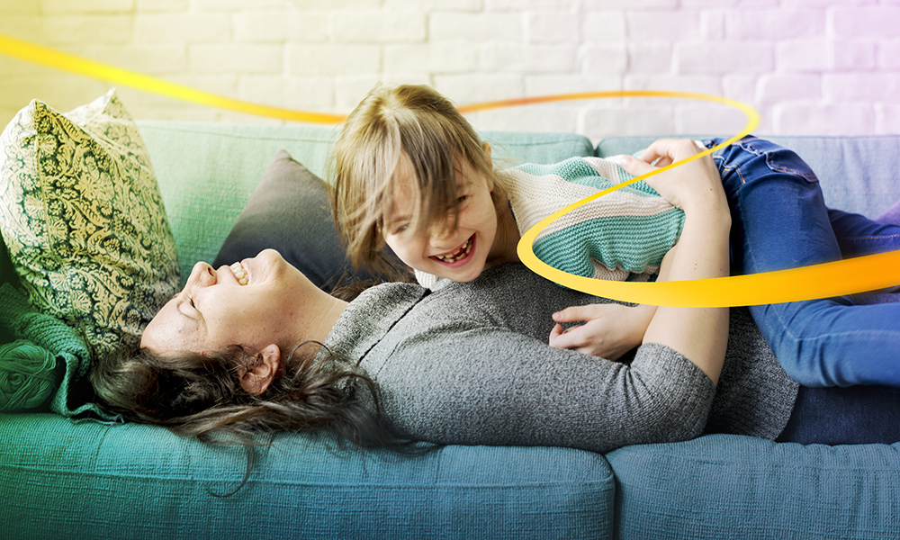 Mother and daughter lying together on sofa laughing and having fun