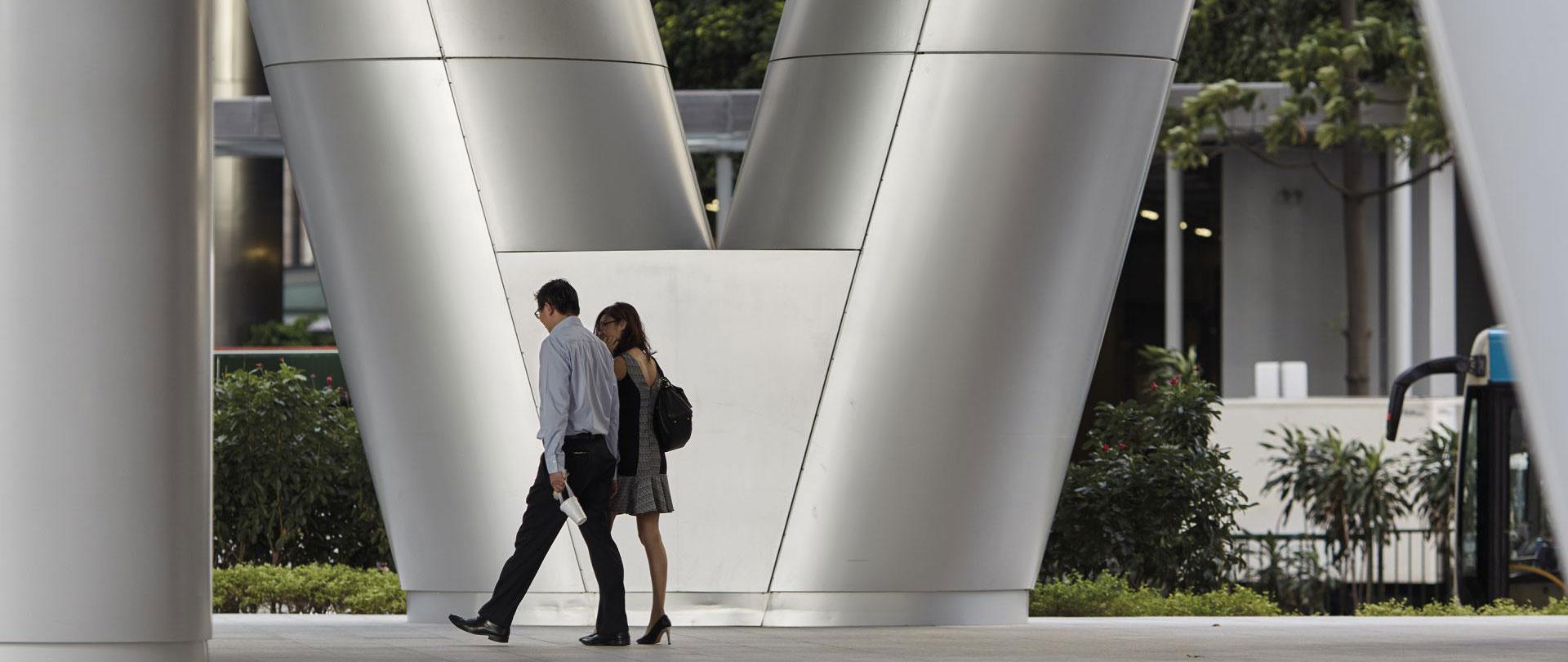 人们走路经过伦敦一栋大型建筑物的图片