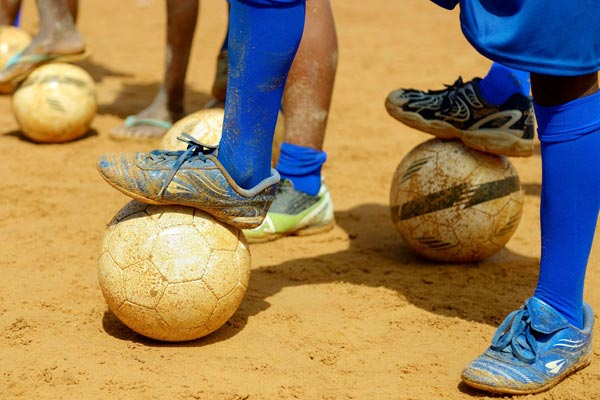 Image of child playing football in the sand